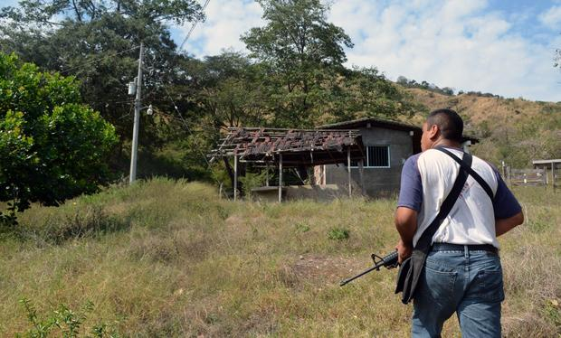 A member of the Mexican federal police inspects an abandoned home during a tour of a ghost pueblo in Tecpan de Galeana, Guerrero state, on Mexico's Pacific Coast. Extortion, threats and killings carried out by a group of heavily armed drug cartel members have emptied out more than 20 small villages in the mountains between the tourist resorts of Acapulco and Ixtapa.