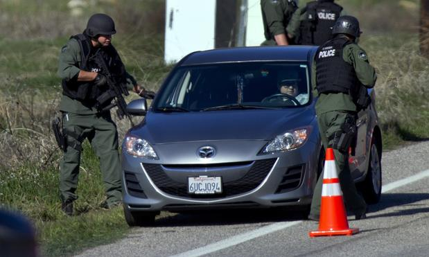 SWAT officers check cars driving south on Highway 38 north of Redlands.