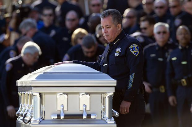 Riverside Police Chief Sergio Diaz put his hand on the casket of slain Riverside Police Officer Michael Crain.