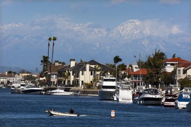 A motor boat cruises Huntington Harbour in Huntington Beach against a backdrop of the recently snowcapped San Gabriel Mountains.