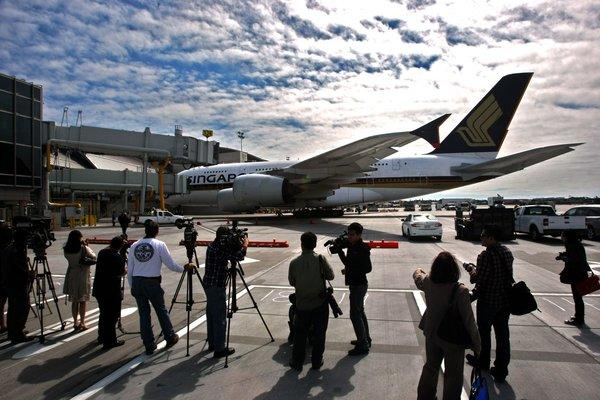 Members of the media watch as a Singapore Airlines A-380 arrives at Gate 134 of the new north concourse of the Tom Bradley International Terminal.