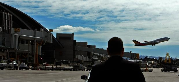 A member of Los Angeles World Airports watches a plane depart behind the new north concourse of the Tom Bradley International Terminal at Los Angeles International Airport. The gates are the first of 18 to be built.