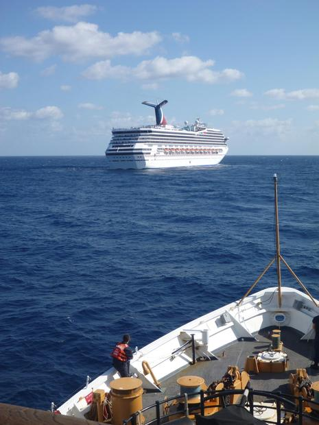 A member of the Coast Guard Cutter Vigorous watches as the cruise ship Carnival Triumph sits idle in the Gulf of Mexico.