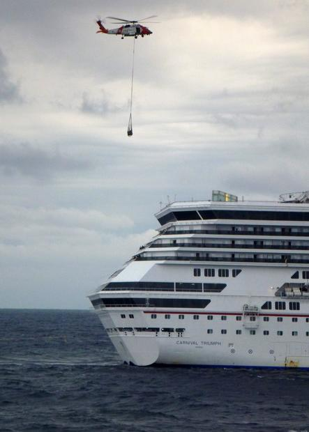A helicopter delivers equipment to the Carnival Triumph cruise ship as it heads to the port in Mobile, Ala. Carnival promised compensation for the more than 3,000 tourists stuck on the ship.