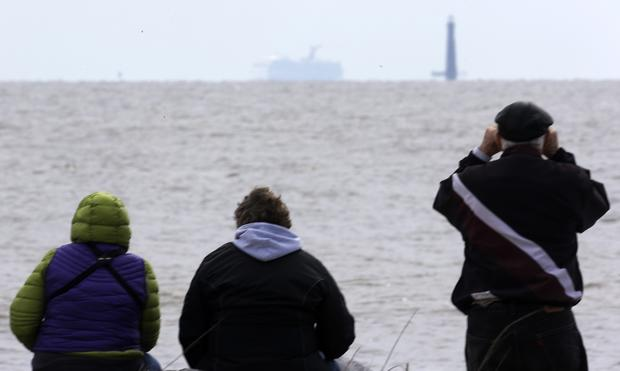 Residents sit on the shore and watch the cruise ship Carnival Triumph near Dauphin Island, Ala. The ship has been idled in the Gulf of Mexico since a fire Sunday in an engine room.