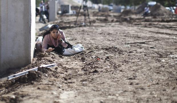 A women takes cover in response to warning sirens in the southern Israeli town of Kiryat Malachi, which has been targeted by rockets fired from the Gaza Strip.