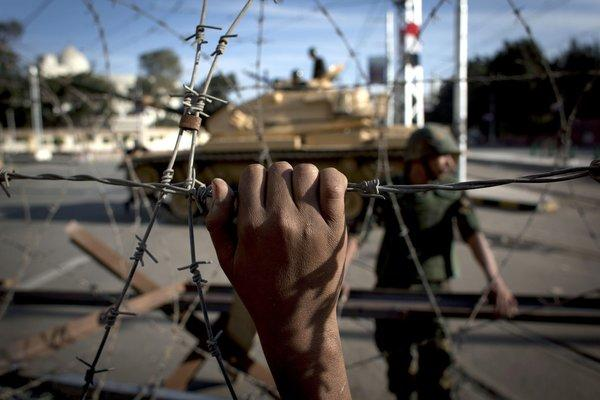 An Egyptian army tank is seen behind barbed wire securing the perimeter of the presidential palace in Cairo while protesters on the other side chant anti-President Mohammed Morsi slogans.