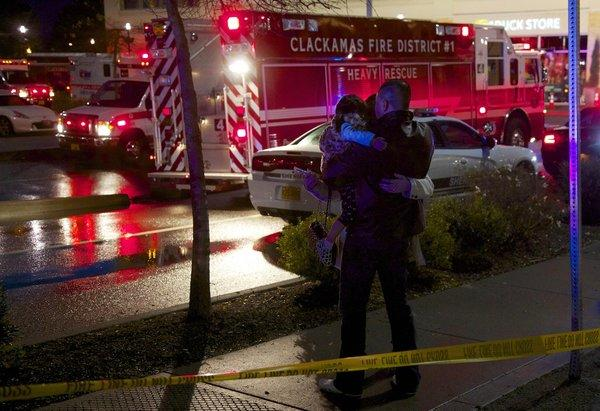 A couple with a child embrace after they were allowed to leave the Clackamas Town Center mall Tuesday.