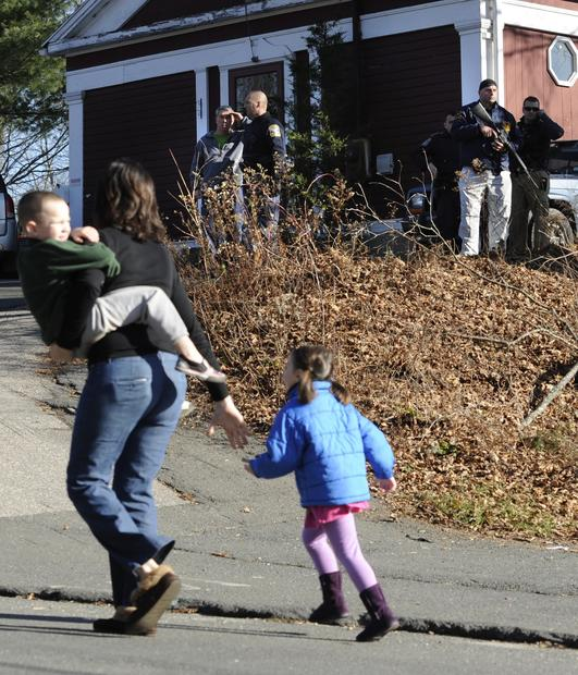 A mother hurries with her children as police look through homes in the area following Friday morning's deadly shooting at the Sandy Hook Elementary School in Newtown, Conn.