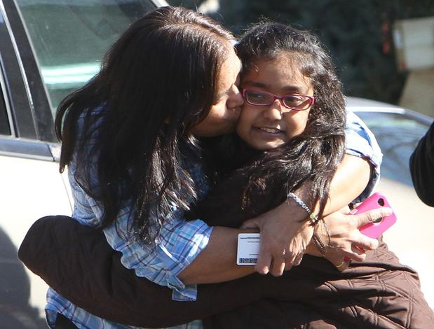 A woman hugs her daughter as they're reunited at the Sandy Hook firehouse after a mass shooting at the local elementary school in Newtown, Conn.