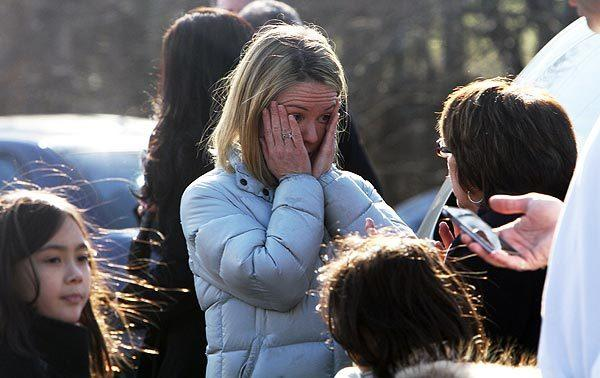 A woman weeps as she arrives to pick up her children at Sandy Hook Elementary School in Newtown, Conn.