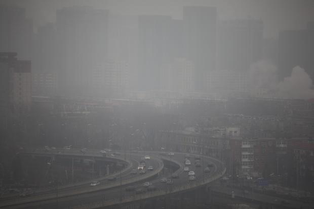 Cars run on an elevated road as buildings in the background are covered in haze Jan. 15. A succession of heavily polluted days has hit Beijing, prompting the government to issue a first ever orange warning. The pollution and poor visibility led to the cancellation of flights, and several schools banned all outdoor activities.