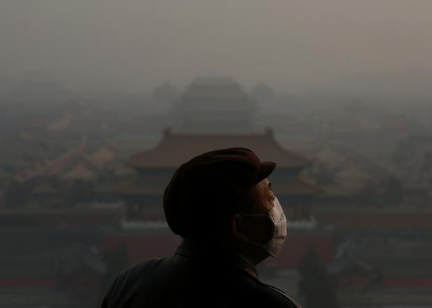 A tourist wearing the mask looks at the Forbidden City in Beijing as pollution covers it Jan. 16. Heavy smog shrouded Beijing as pollution reached hazardous levels days earlier.