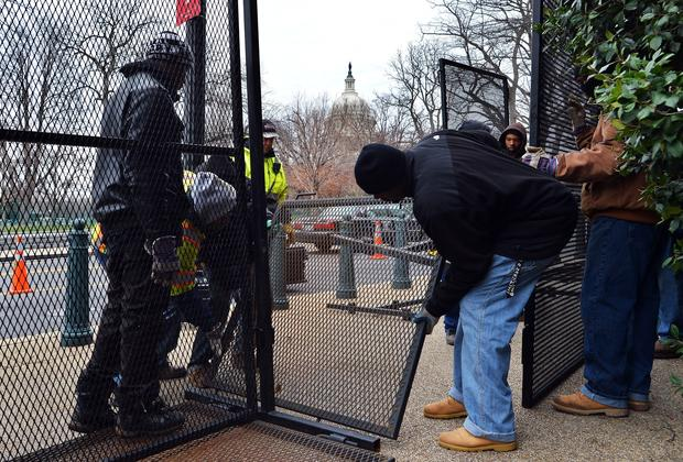 Workers erect a fence around Capitol Hill as preparations continue for the inauguration ceremonies.