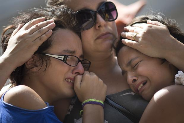 Girls cry in front of a makeshift memorial outside the club.