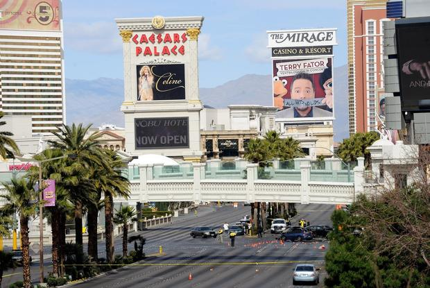 Casino marquees rise above the Las Vegas Strip as investigators work the shooting and crash scene.