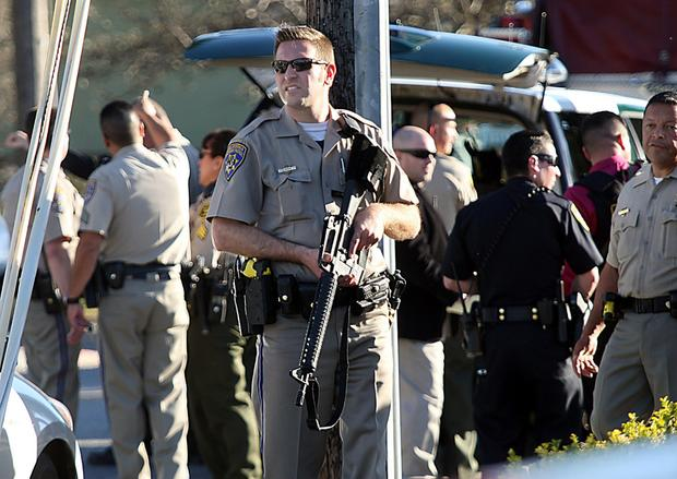 A California Highway Patrol officer carries his rifle near the shooting scene in Santa Cruz, Calif., where two Santa Cruz Police detectives were shot and killed Tuesday, Feb. 26, 2013. The shooting in the community about 60 miles south of San Francisco took place as police were investigating a report of a sexual assault, Santa Cruz County Sheriff Phil Wowak said. A suspect was shot while police were in pursuit of the shooter, the sheriff said. Authorities said that person also died.