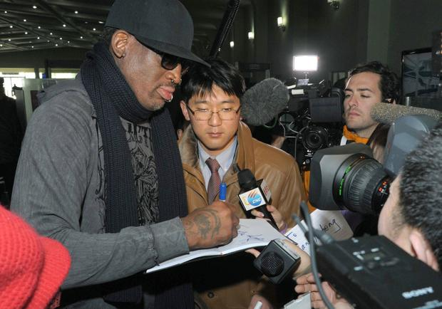Former NBA star Dennis Rodman signs his autograph for a fan at the Pyongyang Airport before he leaves North Korea.