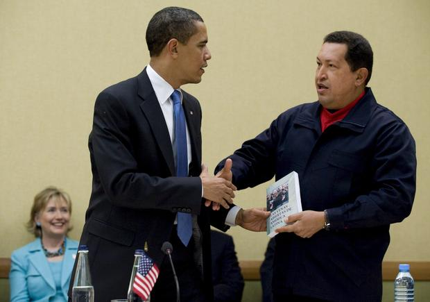 President Obama receives a book from Chavez as Secretary of State Hillary Rodham Clinton looks on during a meeting at the Summit of the Americas in Port of Spain, Trinidad and Tobago.