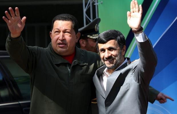 Iranian President Mahmoud Ahmadinejad, right, and Venezuelan President Hugo Chavez wave at the presidential palace in Tehran during a ceremony marking the start of a two-day visit by Chavez in April 2009.