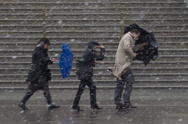 People walk as snow falls during a late-winter storm in Washington, D.C., on Wednesday. Federal offices and many schools have closed in preparation for a mix of snow, sleet and rain that could account for the area's largest winter storm in two years.