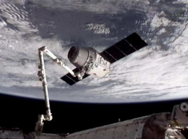 This image provided by NASA-TV shows the SpaceX Dragon commercial cargo craft, top, after Dragon was grappled by the Canadarm2 robotic arm and connected to the International Space Station on Friday. Dragon is scheduled to spend about a week docked with the station before returning to Earth on May 31 for retrieval.
