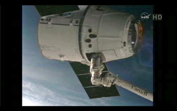 A television still from NASA TV provided by the National Aeronautics and Space Administration (NASA) on 25 May 2012 shows the SpaceX 'Dragon' commercial cargo craft after it was captured by the robotic arm of the International Space Station (ISS) on 25 May 2012. The Dragon spacecraft arrived at the ISS to become the first private craft ever to reach the orbiting laboratory. Dragon had slowly approached the station over the course of several hours, coming to within metres of the ISS, before astronauts inside the station used a robotic arm to grab the craft at 1356 GMT as both craft flew high over Australia.