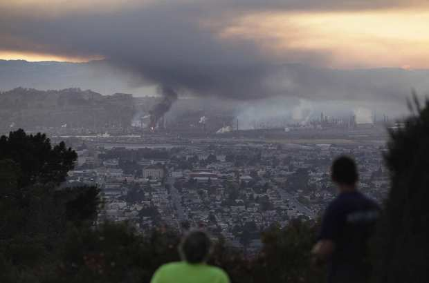 People watch smoke rise from the Chevron refinery in Richmond, Calif., from a vantage point in the hills of nearby El Cerrito in the east San Francisco Bay Area.