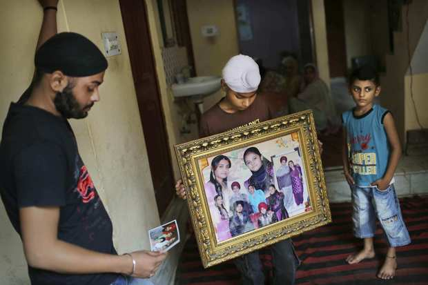 Indian relatives of brothers Sita and Ranjit Singh, who were killed in the shooting attack at a Sikh temple in Wisconsin, look at family photos at the family home in New Delhi on Tuesday. The Indian-born brothers were both killed in the attack Sunday.