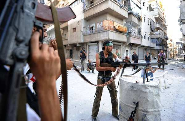 Syrian rebels keep watch during their fight against the Syrian army in a street near Aleppo, Syria on Aug. 12.