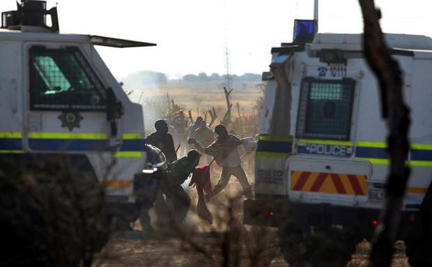 Striking miners throw stones at police as protests become violent at the Lonmin platinum mine near Rustenburg, South Africa.