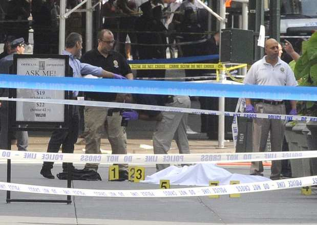 Crime scene technicians work around a covered body on 5th Avenue after the shooting outside the Empire State Building on Friday.