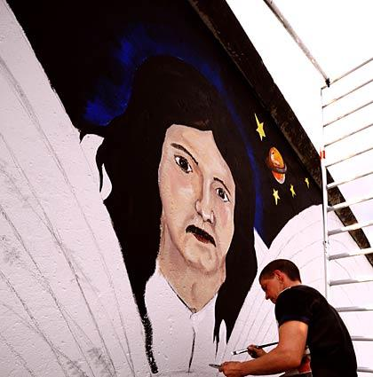 German artist Catrin Resch retouches a mural she painted 19 years ago on the Berlin Wall.