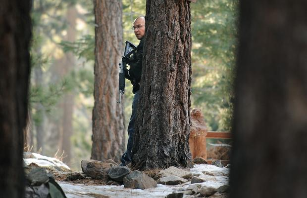 A San Bernardino County sheriff's officer searches for shooting suspect Christopher Dorner in Big Bear Lake.
