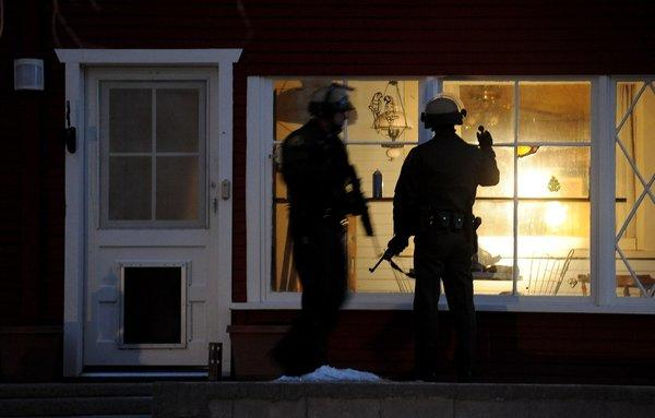 Police officers check a house in Big Bear Lake for shooting suspect Christopher Dorner.