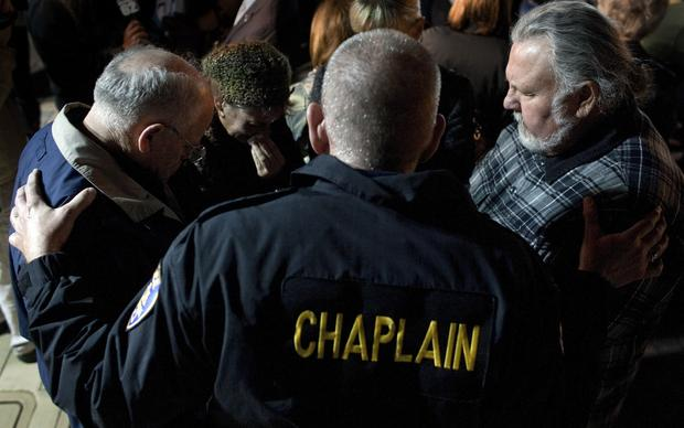 Riverside Police Chaplain Steve Ballinger comforts residents during a vigil at City Hall for the slain and wounded Riverside police officers.