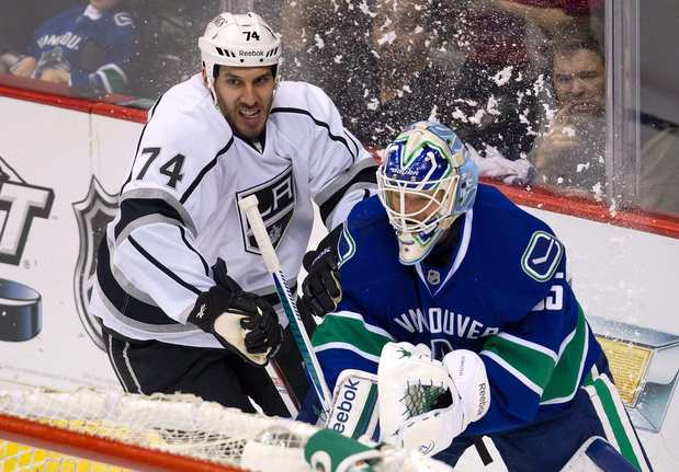 Vancouver goalie Cory Schneider, right, is pressured by Kings forward Dwight King while playing the puck behind the net during the first period of Game 5 of the Western Conference quarterfinals.