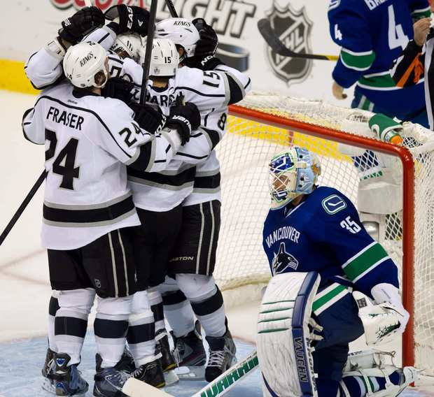 Kings forward Brad Richardson is mobbed by his teammates after scoring on Vancouver goalie Cory Schneider during the third period of Game 5 of the Western Conference quarterfinals.