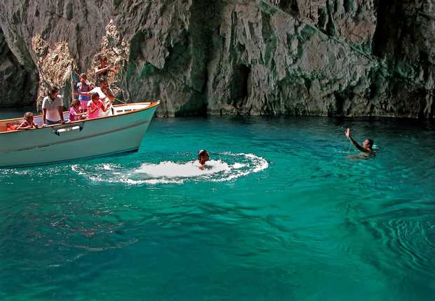 Swimmers and boaters enjoy the emerald water near the Green Grotto, one of Capri, Italy's famous coastal caves. There's also a very popular Blue Grotto.