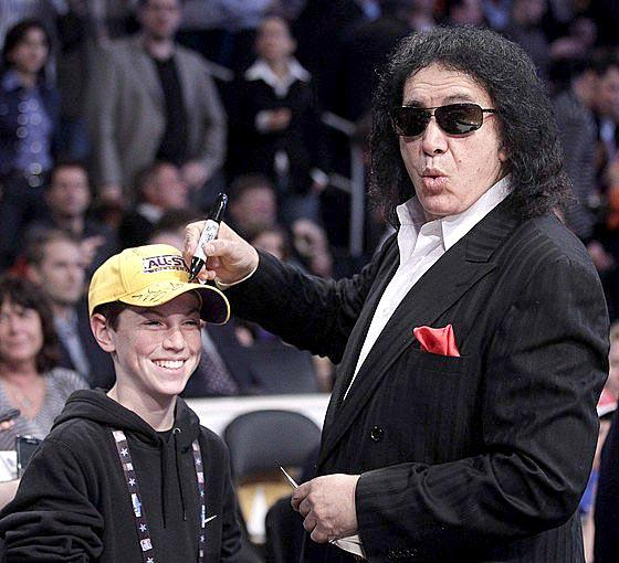 Gene Simmons signs a fan's hat courtside at Staples Center before the start of the NBA All-Star game.