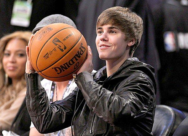 Justin Bieber gets set to throw back the ball from his seat courtside at the NBA All-Star game at Staples Center.