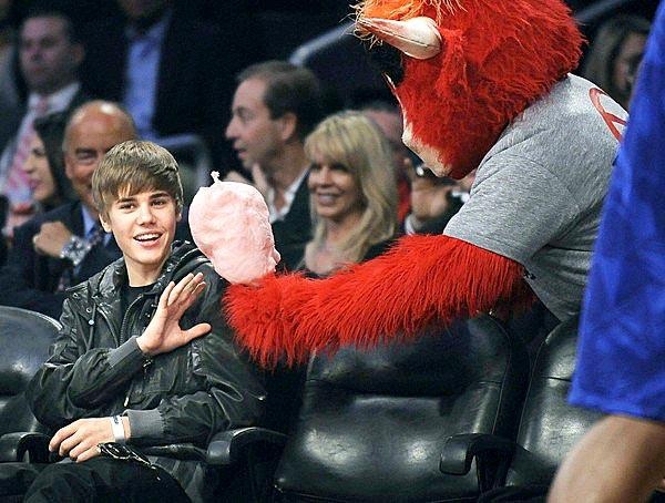 Justin Bieber politely turns down an offer of cotton candy from the Bulls mascot during the NBA All-Star game at Staples Center.