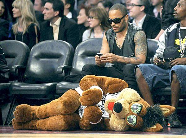 Lenny Kravitz takes care of some business on his phone while the Spurs mascot looks for some attention during the NBA All-Star game at Staples Center.