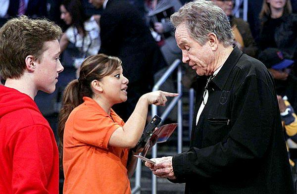 An usher at Staples Center directs Warren Beatty to his seat before the start of the NBA All-Star game.