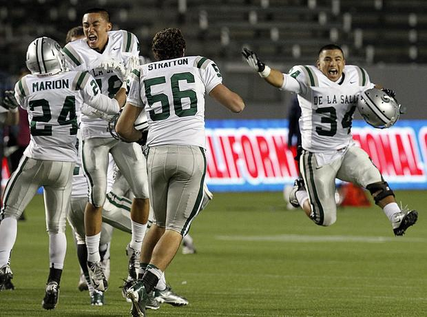 De La Salle players celebrate after defeating Centennial for the school's fourth consecutive CIF state championship Open Division bowl game victory.