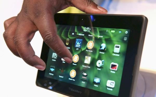 A worker demonstrates the new BlackBerry PlayBook.