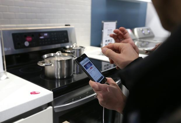 Attendees use a cellphone to operate an LG Smart Oven.