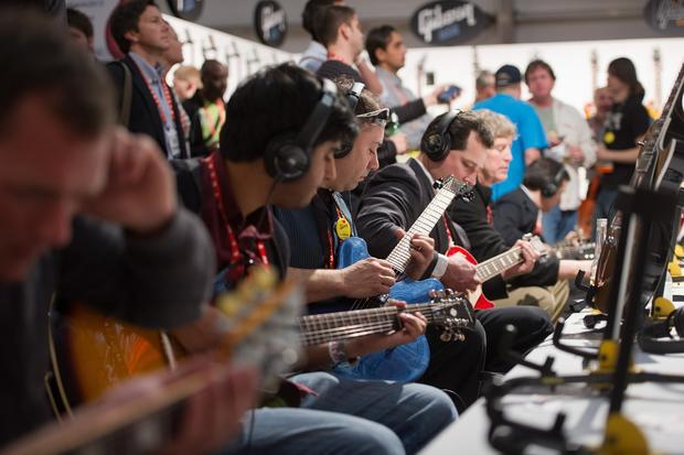 Attendees play Gibson Corp. guitars inside the Gibson tent.