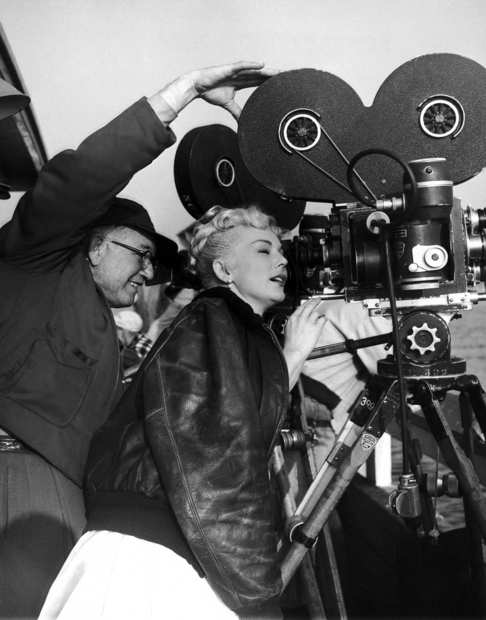 "Camerman Charles Van Enger allows Eva Gabor to look through the camera finder on the Los Angeles set of her film, ""Captain Kidd and the Slave Girl,"" on Dec. 19, 1953."