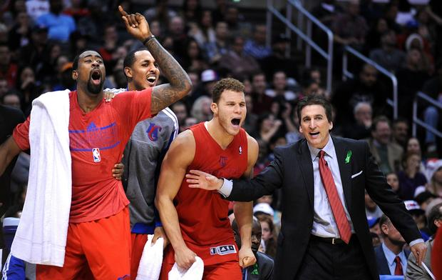Clippers Coach Vinny Del Negro tries to keep (from left) DeAndre Jordan, Ryan Hollins and Blake Griffin from spilling onto the court as they celebrate in the closing minutes of their 112-100 victory over the Nuggets on Tuesday night.